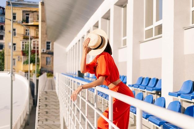 Stijlvolle vrouw in oranje kleding bij zonsondergang bij fietspad stadion poseren Gratis Foto