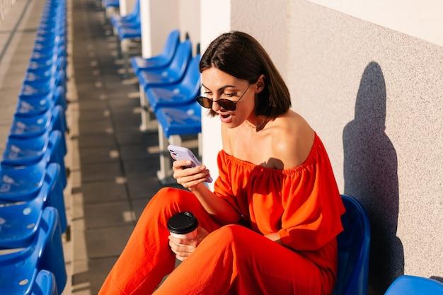 Stijlvolle vrouw in oranje kleding bij zonsondergang in het fietspadstadion met een kopje koffie en een mobiele telefoon die geschokt naar het scherm kijkt