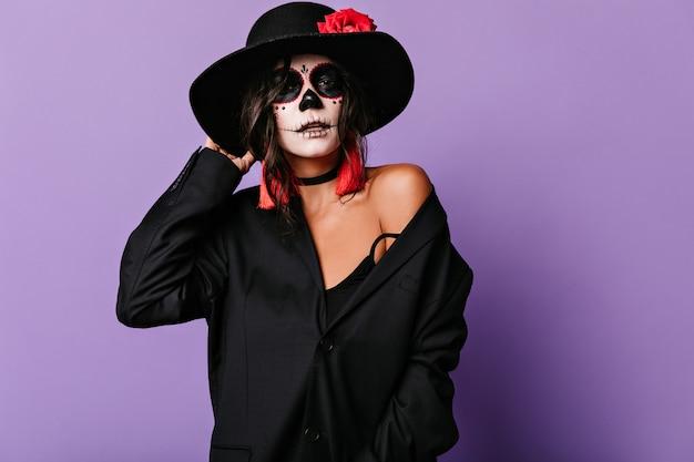 Stijlvolle vrouw in oversized jas en ongebruikelijk halloween-masker raakt hoedrand. portret van aantrekkelijk gelooid meisje op lila muur.