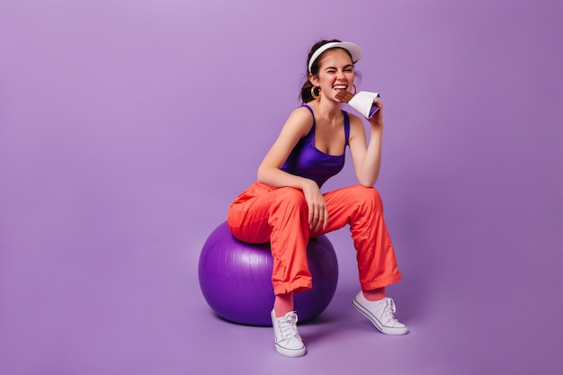 Stijlvolle vrouw in paarse top en rode joggingbroek eet reep chocola zittend op fitball tegen paarse muur