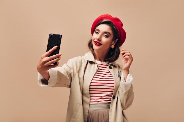 Stijlvolle vrouw in rode baret neemt selfie op beige achtergrond. mooie dame met felle lippenstift met oorbellen en in regenjas maakt foto.
