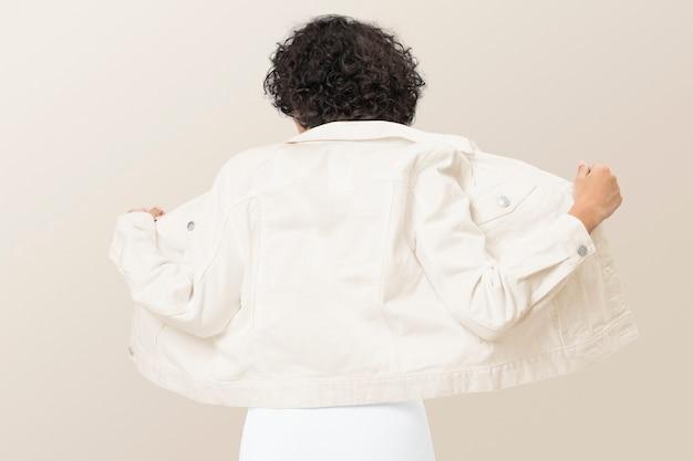 Stijlvolle vrouw in romig spijkerjack voor achteraanzicht van kledingshoot