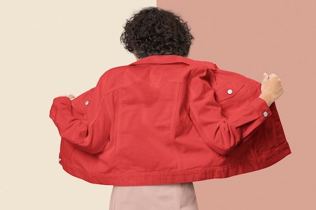 Stijlvolle vrouw in rood spijkerjack voor achteraanzicht van kledingshoot