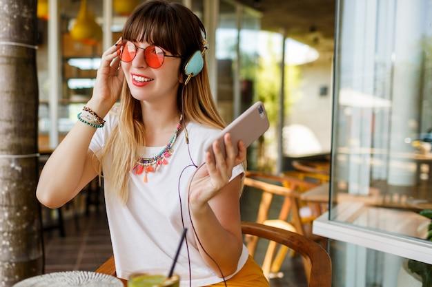 Stijlvolle vrouw in roze bril genieten van groene gezonde smoothie, muziek luisteren door oortelefoons, met mobiele telefoon.