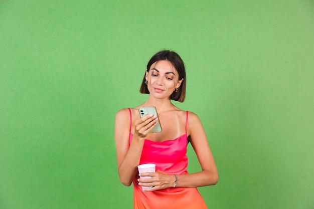 Stijlvolle vrouw in roze zijden jurk geïsoleerd op groen blij met een glimlach op het scherm van de mobiele telefoon, lees berichtnieuws message
