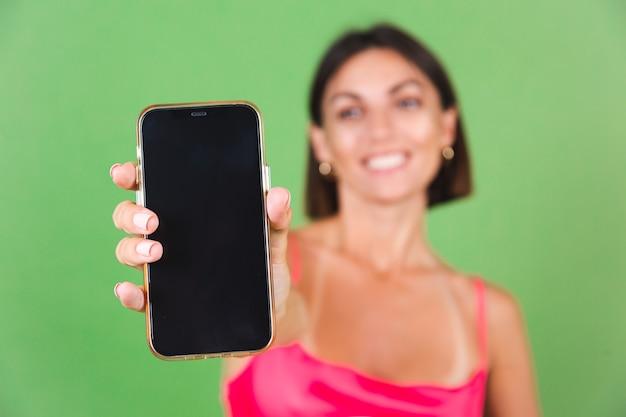 Stijlvolle vrouw in roze zijden jurk geïsoleerd op groen blij opgewonden punt op zwart leeg scherm van mobiele telefoon