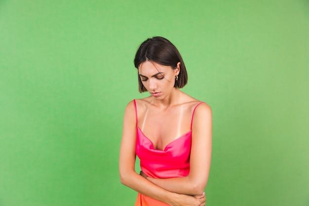 Stijlvolle vrouw in roze zijden jurk geïsoleerd op groen die lijdt aan maagpijn