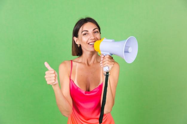Stijlvolle vrouw in roze zijden jurk op groen, blij opgewonden, vrolijk geschreeuw in megafoon, duim omhoog geïsoleerd