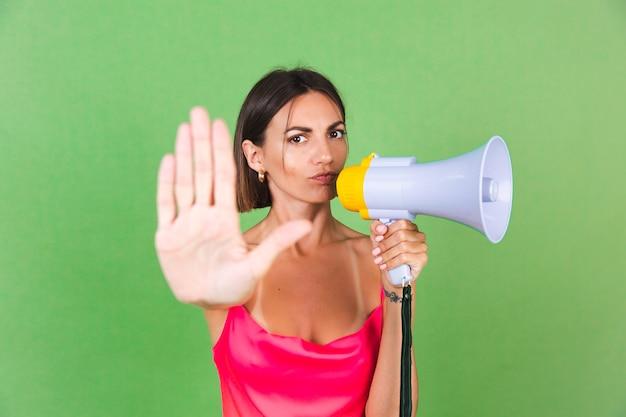 Stijlvolle vrouw in roze zijden jurk op groen, met megafoon, geïsoleerd, stop gebaar met serieus gezicht