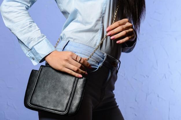 Stijlvolle vrouw in spijkerbroek met kleine zwarte handtas
