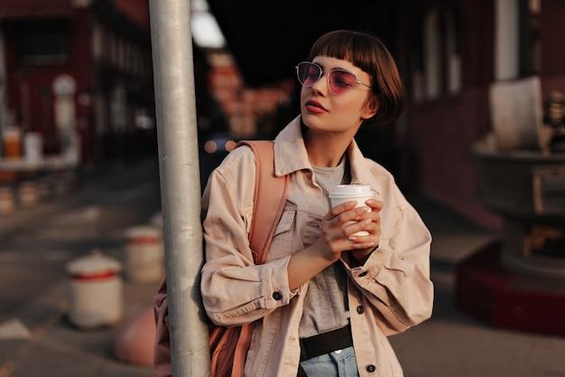 Stijlvolle vrouw in strakke outfit met kopje thee in de stad