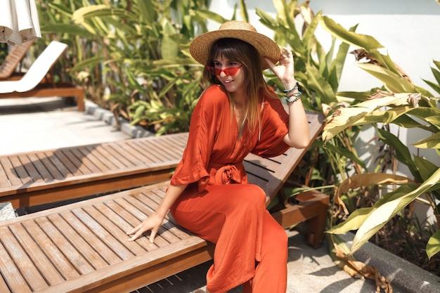 Stijlvolle vrouw in strohoed en oranje playsuit rustend op haar villa tijdens vakantie op bali.