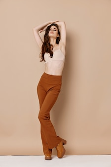 Stijlvolle vrouw in virtualquery-broek houdt haar hand boven haar hoofd. hoge kwaliteit foto