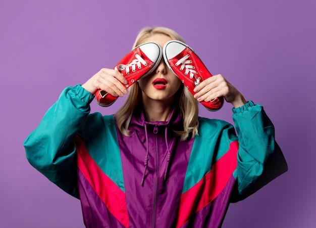 Stijlvolle vrouw in windjack uit de jaren 80 en ronde zonnebril houdt rode gumshoes op paarse muur