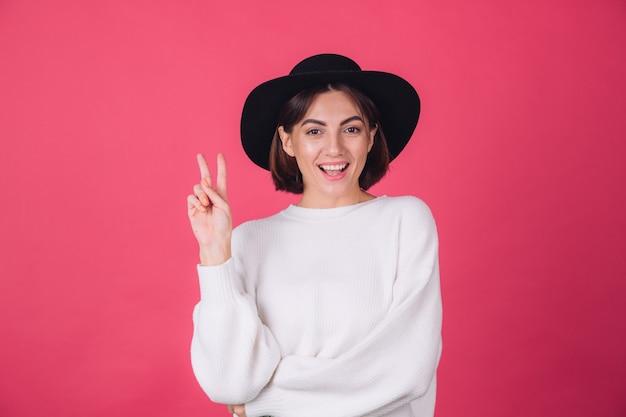 Stijlvolle vrouw in witte casual trui en hoed op rood roze muur