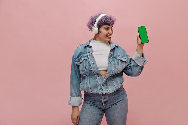Stijlvolle vrouw in witte koptelefoon kijkt naar haar smartphone. vrouw met helder kapsel glimlacht en luistert naar muziek.