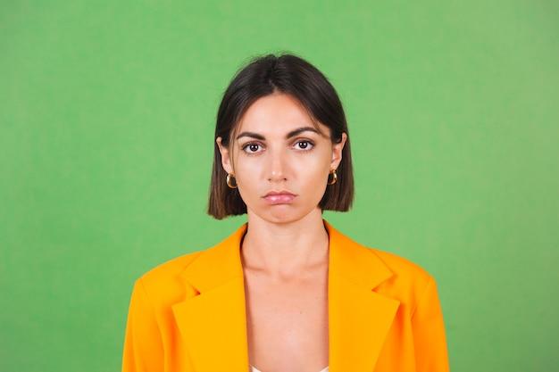 Stijlvolle vrouw in zijden beige jurk en oranje oversized blazer op groen, ongelukkige glimlach naar beneden, kijk naar de camera met droevige ogen