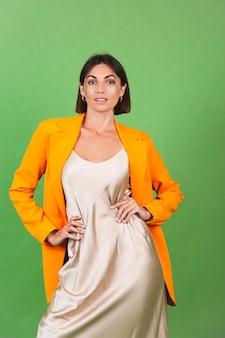 Stijlvolle vrouw in zijden beige jurk en oranje oversized blazer op groen, positieve emoties glimlach