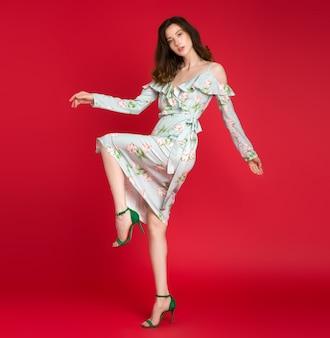 Stijlvolle vrouw in zomer mode trend jurk poseren op rood