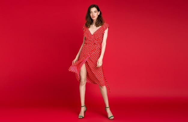 Stijlvolle vrouw in zomer modetrend gestippelde rode jurk poseren op rood