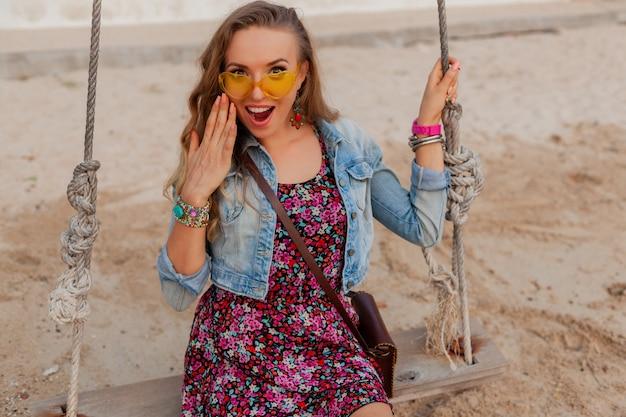 Stijlvolle vrouw in zomerkleding vakantie op strand in kleurrijke gele sunglasess glimlachend gelukkig