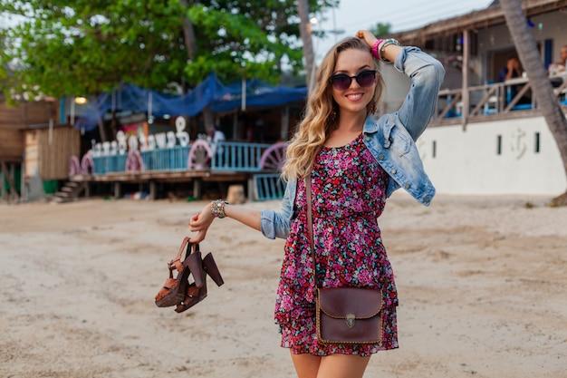 Stijlvolle vrouw in zomerkleding vakantie wandelen op het strand met schoenen in de hand