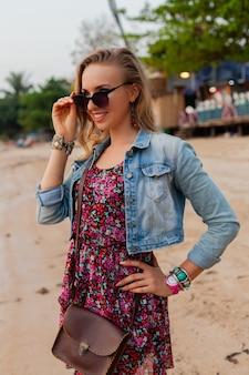 Stijlvolle vrouw in zomerkleding vakantie wandelen op het strand met zonnebril