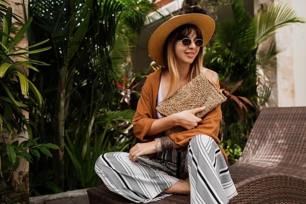 Stijlvolle vrouw in zomerkleren ontspannen in hotel en genieten van trendy zonnebril, strooien hoed en handtas, boheemse armbanden en accessoires.