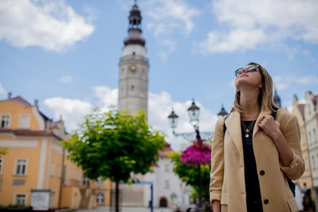 Stijlvolle vrouw in zonnebril en rugzak op het oude stadscentrum