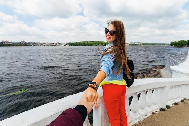 Stijlvolle vrouw in zonnebril met een rugzak in de buurt van het meer
