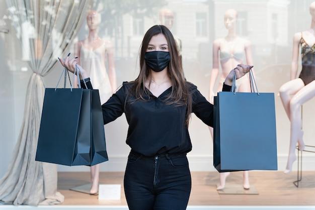 Stijlvolle vrouw in zwarte kleding en beschermend masker houdt zwarte boodschappentassen vast. zwarte vrijdag-concept.