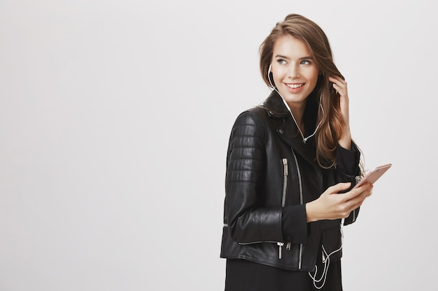 Stijlvolle vrouw linksaf, glimlachend, muziek luisteren en gebruik mobiele telefoon