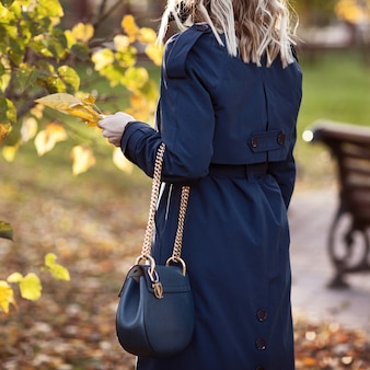 Stijlvolle vrouw loopt in het najaar park.