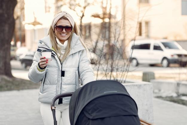 Stijlvolle vrouw lopen in een stad met koets
