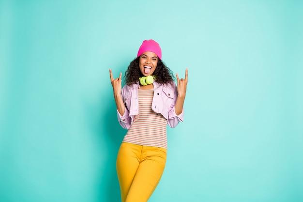 Stijlvolle vrouw met afrokapsel poseren tegen de blauwe muur