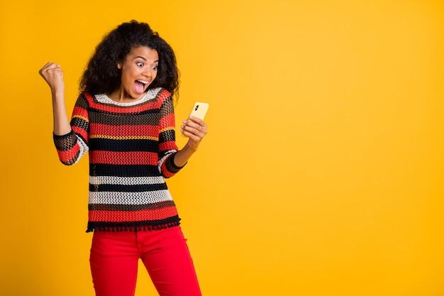 Stijlvolle vrouw met afrokapsel poseren tegen de oranje muur