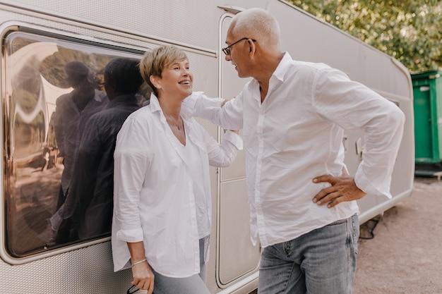 Stijlvolle vrouw met blonde haren in witte blouse en spijkerbroek lachen en kijken naar grijze harige man in licht overhemd buiten.