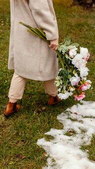 Stijlvolle vrouw met boeket bloemen buiten in de lente