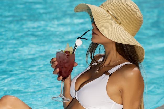 Stijlvolle vrouw met cocktail in de buurt van zwembad