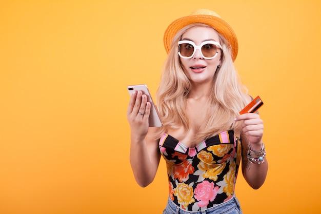 Stijlvolle vrouw met creditcard en telefoon in studio over gele achtergrond