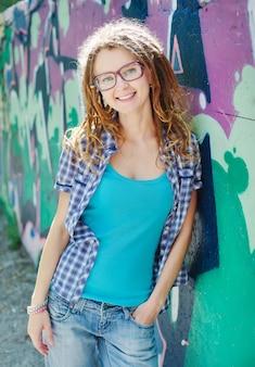 Stijlvolle vrouw met dreadlocks, achtergrondmuur met graffiti