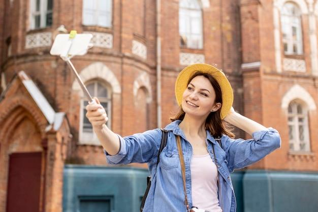 Stijlvolle vrouw met hoed buitenshuis een selfie te nemen