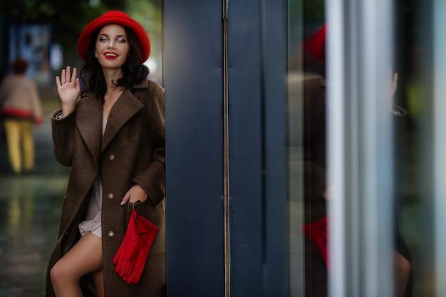 Stijlvolle vrouw met lichte avond make-up in rode handschoenen en een rode avond hoed in de stad in een herfst jas