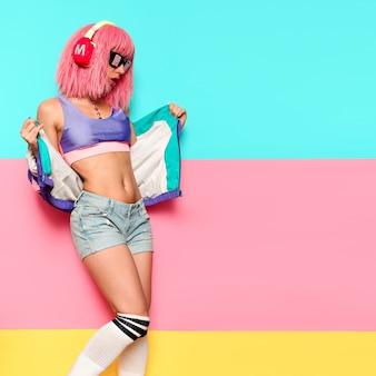 Stijlvolle vrouw met roze haren en koptelefoon