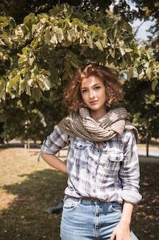 Stijlvolle vrouw onder boom in park