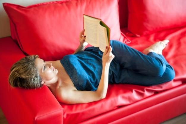 Stijlvolle vrouw ontspannen lezen op een rode sofa