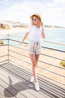 Stijlvolle vrouw op het strand van de zomer op een warme dag in zomerhoed en zonnebril