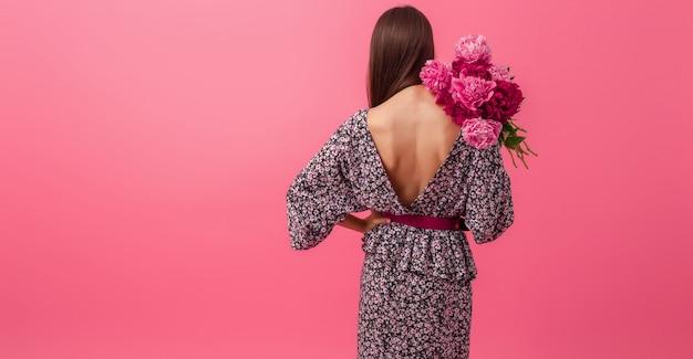 Stijlvolle vrouw op roze in trendy zomerjurk poseren met peony bloemen boeket, uitzicht vanaf achterkant