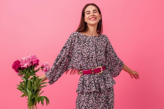 Stijlvolle vrouw op roze in trendy zomerjurk poseren met peony bloemen boeket