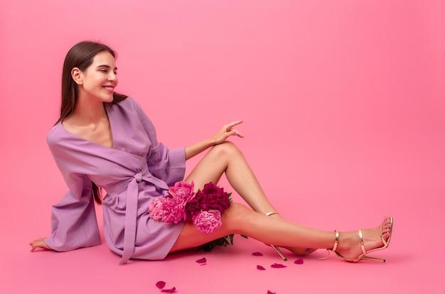 Stijlvolle vrouw op roze in zomer violet mini trendy jurk poseren met peony bloemen boeket zittend op de vloer